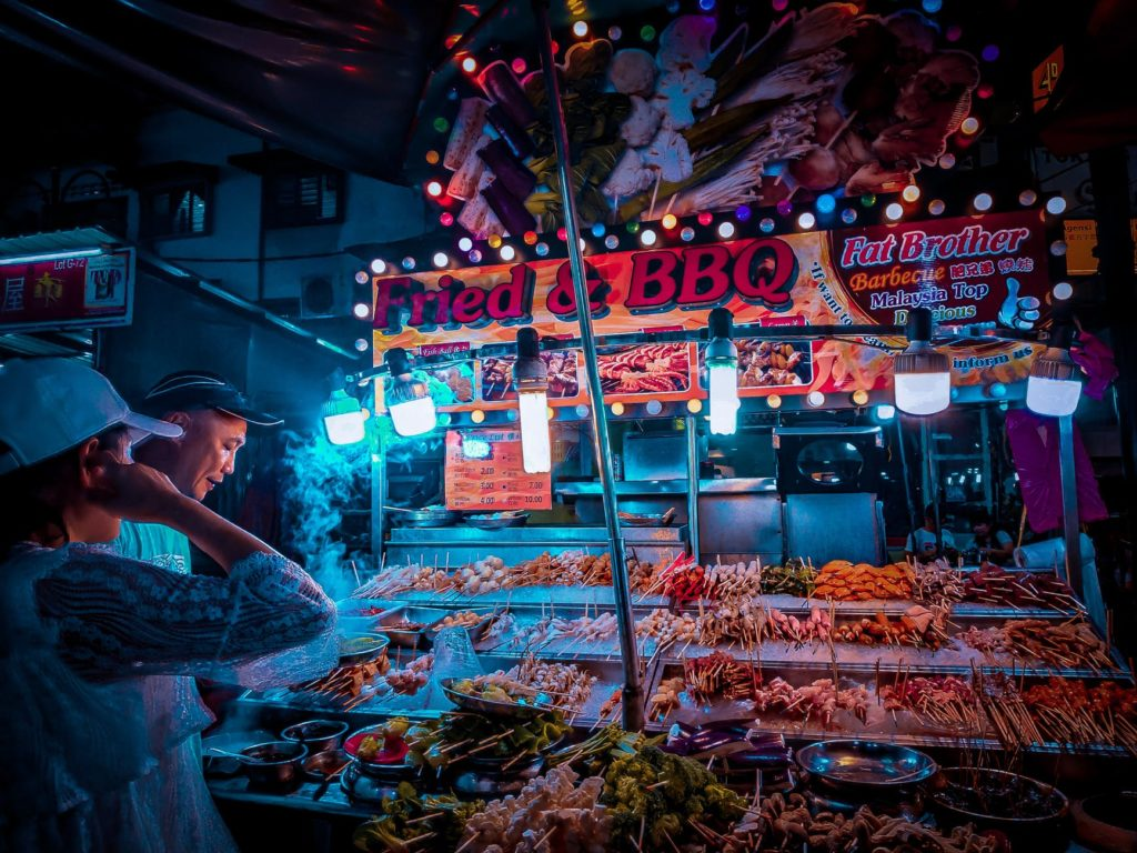 customer choosing raw kebab in street stall at night